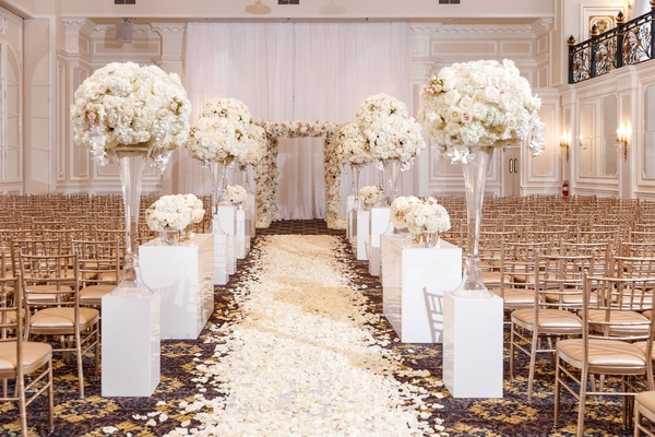 ballroom wedding ceremony gold chairs white risers flower arrangements rose petal aisle