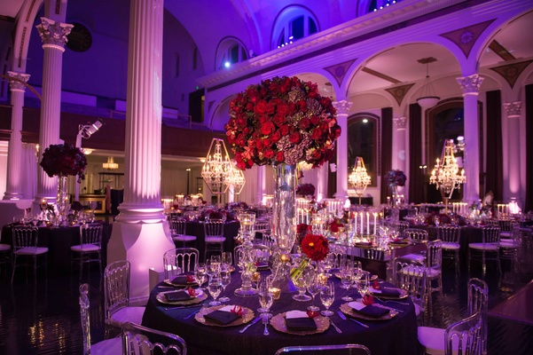 Vibiana wedding reception with round purple table and tall red flower arrangement centerpiece