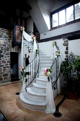 Chateau staircase with white drapes and flower arrangements