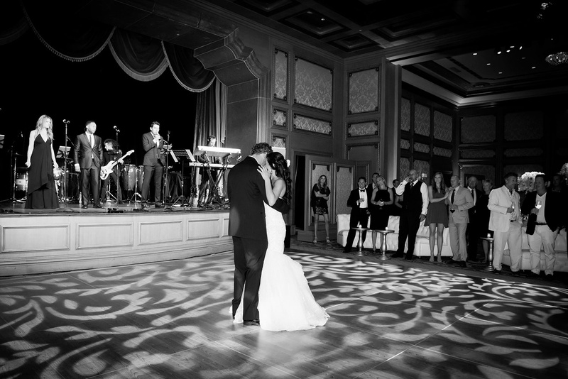 Black and white photo of bride and groom sharing their first dance on gobo projection dance floor