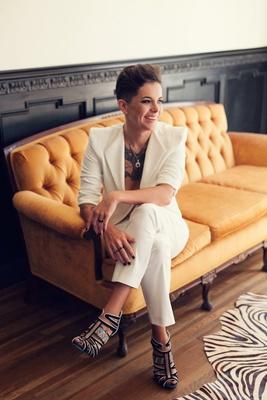 Bride wears an ivory blazer, Calvin Klein cropped pants, black & white heels sits on a yellow sofa