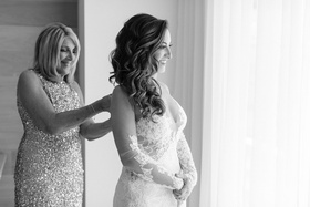 Black and white photo of mother of bride helping daughter into ines di santo wedding dress bridal