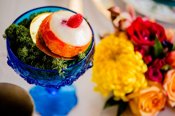 slice of white peach with raspberry on gold disk set on bed of green moss in blue goblet