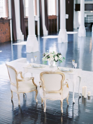 Sweetheart table with vintage chairs on Vibiana dark hardwood floor stage