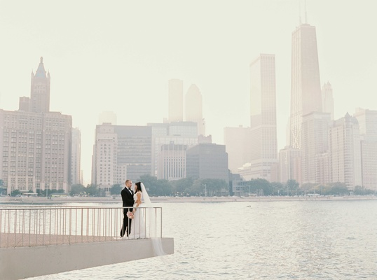 Bride and groom on ledge over river in Chicago with skyline in background