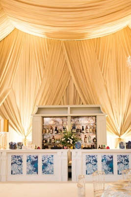 Wedding bar at tent reception blue white motif clear chairs tent ceiling tall wedding structure