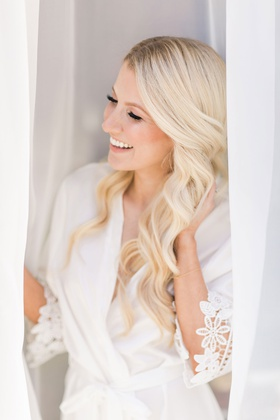 wedding day getting ready long blonde curled hair white robe graphic lace trim curtains