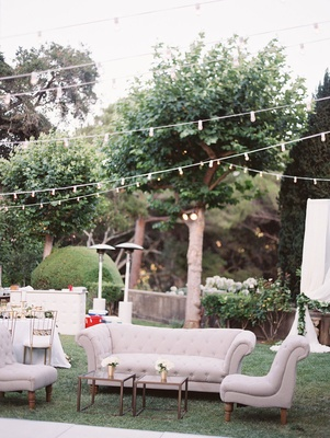 outdoor lounge area with tan furniture small glass coffee tables low florals under string of lights