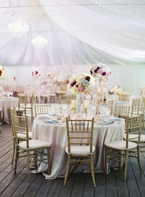 Round wedding table with gold chairs, light blue napkins, and pastel tall flower arrangements