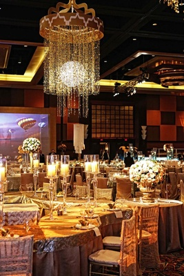 Houston indian wedding celebration with 800 person guest list wedding reception with tables covered in gold tablecloths and topped with tall candleholders junglespirit Choice Image