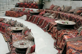 Amphitheater ceremony seating covered with patterned blankets and pillows