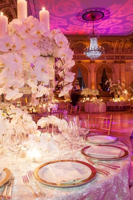 Wedding reception table with gold-rimmed chargers and white orchid arrangements
