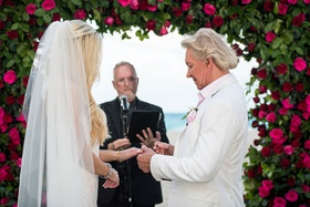 bride with long blonde hair and veil groom in white jacket pink shirt putting ring on bride's finger
