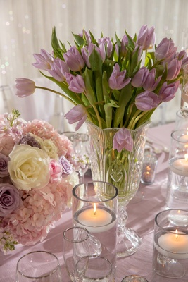 Wedding reception low centerpiece purple tulip flowers next to floating candles low centerpiece