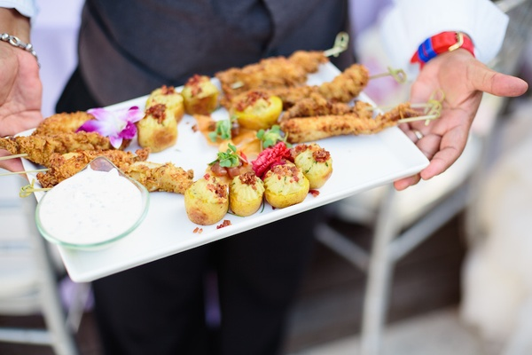 Wedding cocktail hour with passed skewered appetizers and small bites on rectangular tray