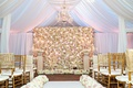 Chapel with white drapery, flower wall, chandelier, gold chiavari chairs at Tracy Morgan wedding
