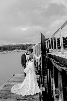 black and white photo of bride in berta wedding dress and groom in tuxedo on dock