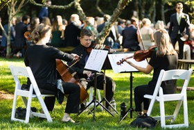 wedding ceremony musicians violin cello viola in white chairs on lawn greenery