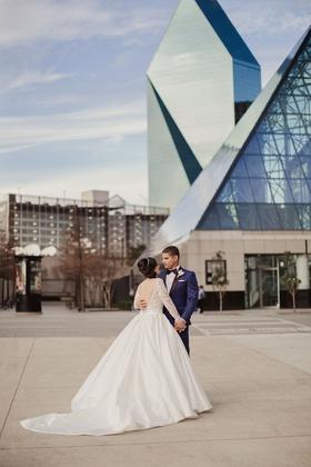 Wedding venue in Dallas Texas bride in low back long sleeve ball gown groom in navy tuxedo