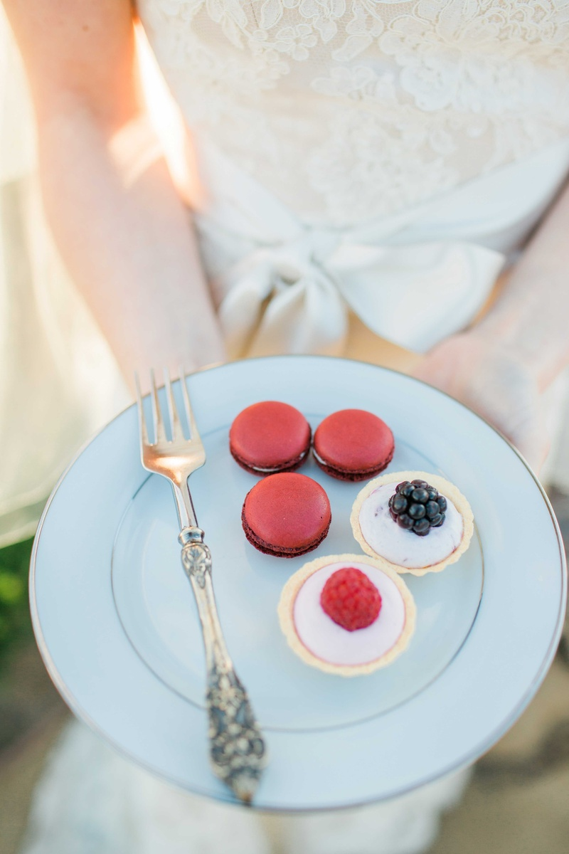 bride holding plate of red french macarons fruit tarts desserts on white china