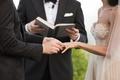 groom in Ermenegildo Zegna puts ring on bride in blush mark ingram gown