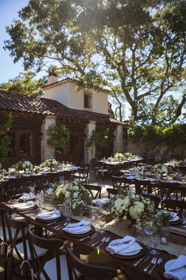 Outdoor wedding reception with wood tables, chairs, white roses, hydrangeas, greenery at Holman Ranc