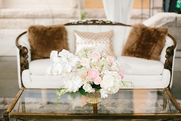 cream sofa with fur pillows, glass table with florals, blue garden roses, white orchids