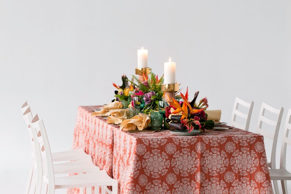 wedding reception styled shoot white chairs orange linen pattern bird of paradise palm green