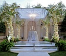 Alfresco ceremony canopy with floral-embellished pillars