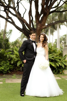 strapless ball gown and groom in black tuxedo