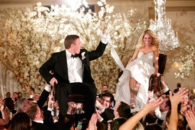 Groom in a black tuxedo & bride in a strapless Pnina Tornai dress hora dance