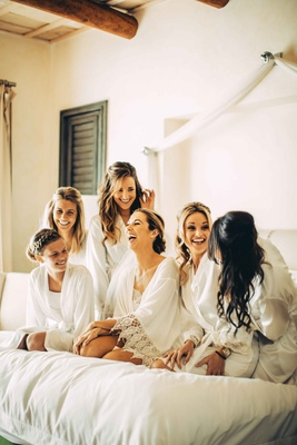 bride bridesmaids pose bed getting ready robes destination wedding mexico morning of
