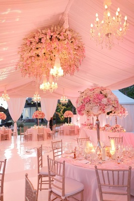 Pink lighting for tent wedding in Bali with lots of flowers