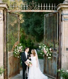 Bride in strapless Monique Lhuillier wedding dress in front of iron gates at wedding venue flowers