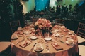 Golden table with pink centerpiece in front of aquarium