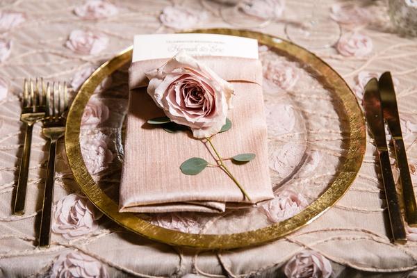 wedding reception light pink linens rosette textured gold charger plate gold flatware pink rose