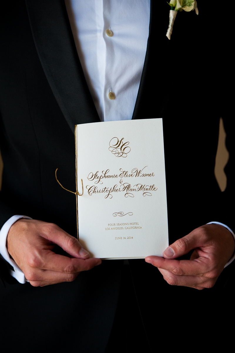 Groom holding white ceremony program with gold lettering