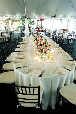 Oval table with white linens and colorful flowers