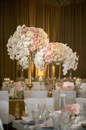 centerpieces with white orchids, blush, cream, and peach roses, gold stands