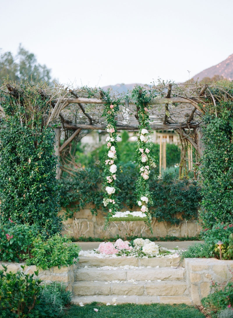 Wedding swing made of moss, green garland, flowers suspended from wood trellis at San Ysidro Ranch