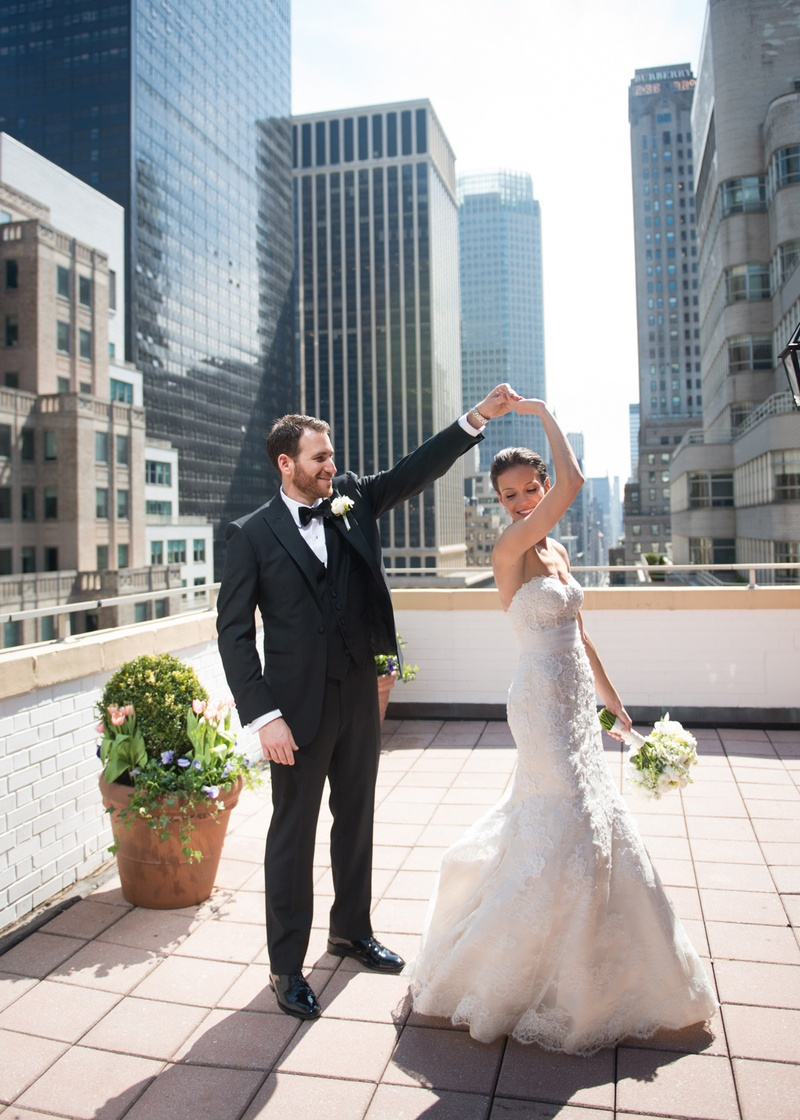 groom in a black tuxedo twirling his bride clad in a white wedding gown on a rooftop in nyc