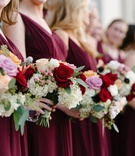 Bridesmaids in burgundy dresses with colorful bouquets red pink white and greenery