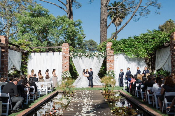 wedding ceremony belmond el encanto lily pond aisle with lily pads on both sides and guest chairs