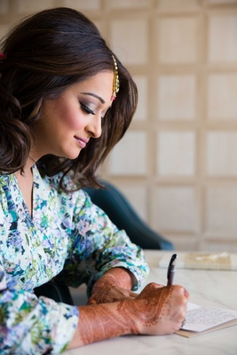 Indian wedding bride with henna on hands writing note to groom on wedding day in floral print robe