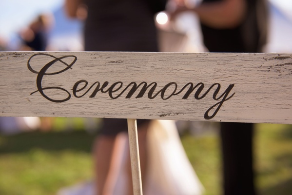 Wood ceremony sign at rustic outdoor wedding on Martha's Vineyard