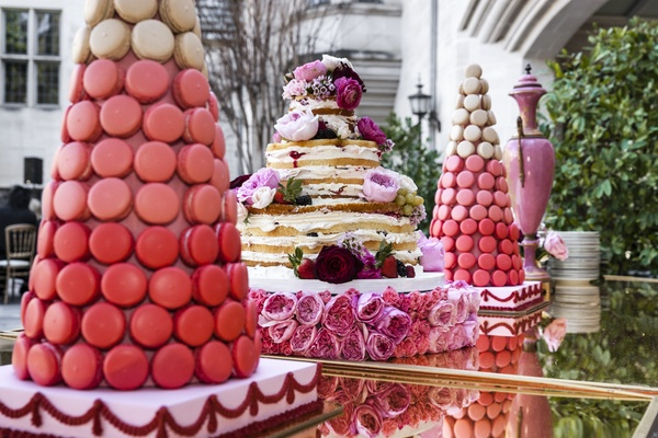 Tree of pink macarons and naked cake on table