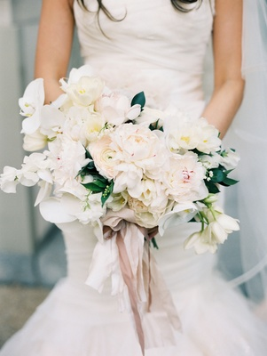 Light white bright bouquet with flowers tied with ribbon held by bride in mermaid wedding dress