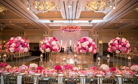 wedding reception ballroom pink flowers gold chairs large dance floor ballroom chandelier