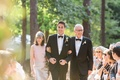 Groom in tuxedo and rustic boutonniere walking down aisle outdoor wedding with mother father jewish