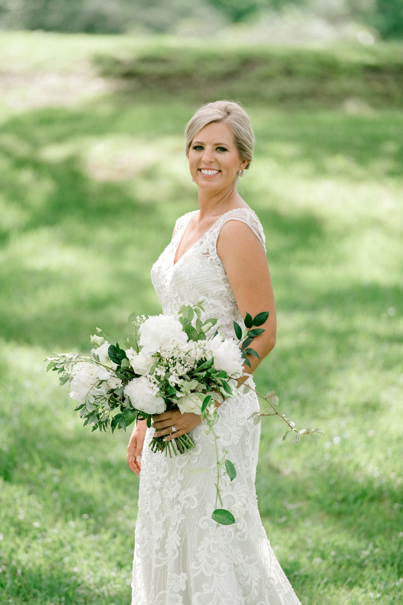 bride in beaded embroidery wedding dress v neck updo white peony greenery leaves bouquet garden